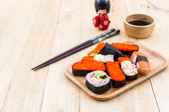 Japanese sushi traditional food on wooden plate with kokeshi. Royalty Free Stock Photos