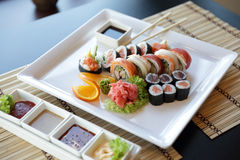 Japanese Sushi. Traditional Japanese sushi on a white plate with vegetables and japanese sauce stock photo
