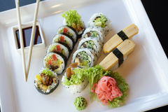 Japanese Sushi. Traditional Japanese sushi on a white plate with vegetables and japanese sauce Royalty Free Stock Photography