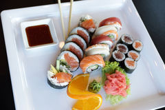Japanese Sushi. Traditional Japanese sushi on a white plate with vegetables and japanese sauce Royalty Free Stock Photos