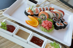 Japanese Sushi. Traditional Japanese sushi on a white plate with vegetables and japanese sauce Stock Image