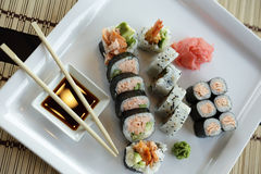 Japanese Sushi. Traditional Japanese sushi on a white plate with vegetables and japanese sauce Royalty Free Stock Images