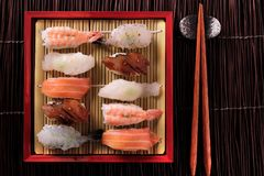 Japanese sushi various assortment red bamboo tray chopsticks above top flat view Stock Photography