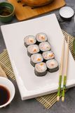Japanese sushi on a white plate with chopsticks and soy sauce stock photo