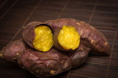 Japanese sweet potato. Burned Japanese sweet potato on bamboo mat, with vignette Stock Photography