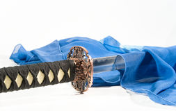 Japanese sword and a blue silk scarf. Close-up of a Japanese sword and a blue silk scarf (on white Royalty Free Stock Photos