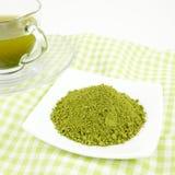 Japanese tasty matcha green tea powder. The Japanese matcha green tea powder on mini white dish and the cup of Japanese tasty matcha green tea on green cotton Royalty Free Stock Photography