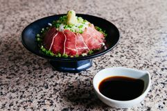 Japanese Tataki raw beef cuisine with ginger, onion, spring onion and soy sauce set on red wooden tray. Beautiful Japanese Tataki raw beef cuisine in black bowl royalty free stock photography
