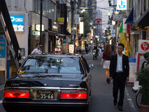 Japanese Taxi in Osaka Street. A Japanese Taxi edges down a street in Osaka at dusk Royalty Free Stock Image