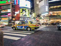 Japanese Taxi in Shibuya Crossing. A famous Japanese yellow cab streaks across the famous Shibuya crossing in Tokyo, Japan Royalty Free Stock Photo