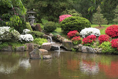 Japanese tea house gardens and fountain in spring. The Shofuso Japanese tea house gardens in spring azalea blooms with stone lanterns and koi pond stock image