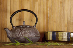 Japanese tea pot and bamboo background. Red Japanese tea serving dish and bamboo Stock Photos