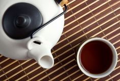 Japanese teapot and teacup on bamboo mat Stock Photo
