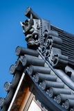 Japanese Temple Roof. The onigawara (ogre) at the end of a Buddhist temple roof in Japan against a blue sky Royalty Free Stock Photos
