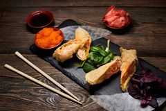 Japanese tempura dish with green, red basil, rice paper on stone plate. Sauce, bamboo chopsticks on wood table. Top view. Asian dish serving with green, red stock photos