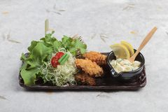 Japanese tempura mussel is deep fried mussel mixing with flour served with egg salad. Japanese tempura mussel is deep fried mussel mixing with flour served with Royalty Free Stock Photography