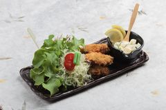 Japanese tempura mussel is deep fried mussel mixing with flour served with egg salad. Japanese tempura mussel is deep fried mussel mixing with flour served with Royalty Free Stock Image