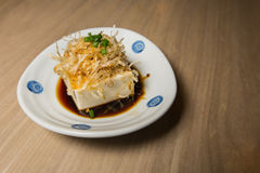 Japanese tofu, Japanese soft cold tofu. With sauce in a dish on dining table Royalty Free Stock Images