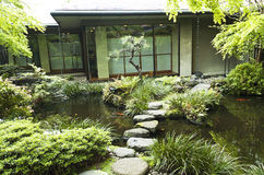 Japanese Tokyo tea house with koi pond. Japanese Tokyo tea house with red koi in a pond and step stone rocks Royalty Free Stock Photography