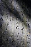 Japanese tombstone in dappled light. Detail of embossed letters on a Japanese tombstone stock photos