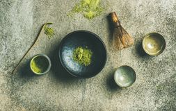 Japanese tools for brewing matcha green tea, grey concrete background. Flat-lay of Japanese tools for brewing matcha tea. Matcha powder in tin can, Chashaku stock photography
