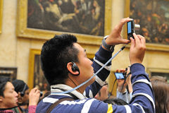 A Japanese tourist take pictures at the Louvre Museum Royalty Free Stock Image