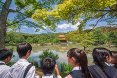 Japanese tourists visiting Golden Pavillion. KYOTO, JAPAN - JUNE 10: Unidentified children visit Golden Pavillion in Kinkakuji temple, Kinkakuji temple is one of Royalty Free Stock Photos