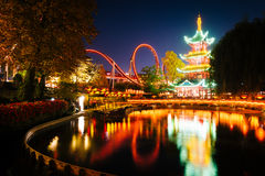 The Japanese Tower and rides at night, reflecting in a lake at T Royalty Free Stock Photo