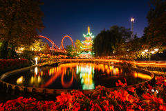 The Japanese Tower and rides at night, reflecting in a lake at T Royalty Free Stock Images