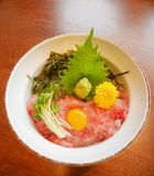 Japanese traditional cuisine minced raw tuna belly on rice bowl maguro don with egg yolk, bean sprouts, wasabi. Perilla leaf shiso, shreded dried seaweed and royalty free stock photo