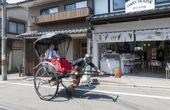 Japanese traditional hand pulled rickshaw carrying tourists on Matsubara street in Kyoto, Japan Stock Image