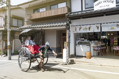 Japanese traditional hand pulled rickshaw carrying tourists on Matsubara street in Kyoto, Japan Royalty Free Stock Photography