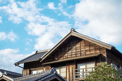 Japanese traditional historical wooden old house under golden sun and morning blue cloudy sky in Japan Stock Images
