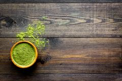 Japanese traditional product. Matcha green tea in bowl and scattered on dark wooden background top view copy space. Japanese traditional product. Matcha green royalty free stock image