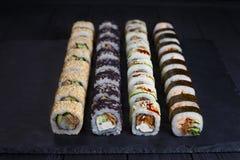 Japanese traditional sushi rolls set with smoked eel fillings on. Black stone slate, close up. Japanese food, sushi restaurant Stock Photo