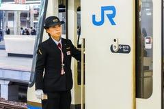 Japanese Train Conductor. KOBE, JAPAN - NOVEMBER 17: Train conductor in Kobe, Japan on November 17, 2013. Unidentified train conductor observes for passengers Stock Image