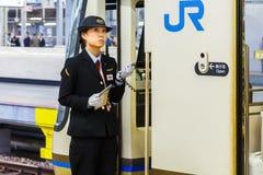 Japanese Train Conductor. KOBE, JAPAN - NOVEMBER 17: Train conductor in Kobe, Japan on November 17, 2013. Unidentified train conductor announces train schedule Stock Image