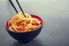 Japanese udon noodles with chopstick. And red pepper on a background. spicy japanese meal Royalty Free Stock Photography