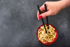 Japanese udon noodles with chopstick. And red pepper on a background. spicy japanese meal Royalty Free Stock Photo