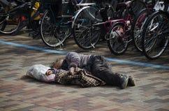 Japanese vagabond people sleeping on floor in public park in mor Royalty Free Stock Image