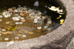 A japanese water filled bowl carved out of  stone with coins Stock Photo