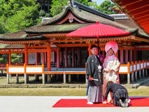 Japanese wedding in traditional costumes. Japanese spouses wearing national traditional costumes on their wedding day in Itsukushima Shinto Shrine Miyajima stock images