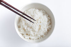 Japanese white rice in ceramic bowl and chopsticks from above Royalty Free Stock Image