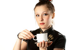 Japanese woman. Portrait of a girl in national japanese clothes with a cup of tea. White background. Studio shot Royalty Free Stock Photos