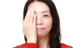 Japanese woman covering one eye with her hand Stock Photos