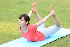 Japanese woman doing yoga bow pose Stock Photography