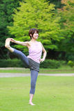 Japanese Woman Doing YOGA Extended Hand-To-Big-Toe Pose. Portrait of Japanewe woman doing yoga exercise outdoor royalty free stock photography