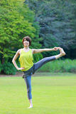 Japanese Woman Doing YOGA Extended Hand-To-Big-Toe Pose. Portrait of Japanewe woman doing yoga exercise outdoor stock image