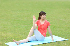 Japanese woman doing yoga Half Lord of the Fishes pose Stock Photos
