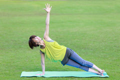 Japanese Woman Doing YOGA Side Plank pose. Portrait of Japanewe woman doing yoga exercise outdoor Stock Images